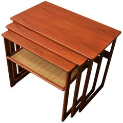 Danish Modern Set of Three Larger Teak Nesting Tables with a Woven Cane Shelf