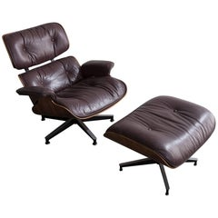 """670"" Lounge Chair and Ottoman in Rosewood with Aubergine Leather Upholstery"