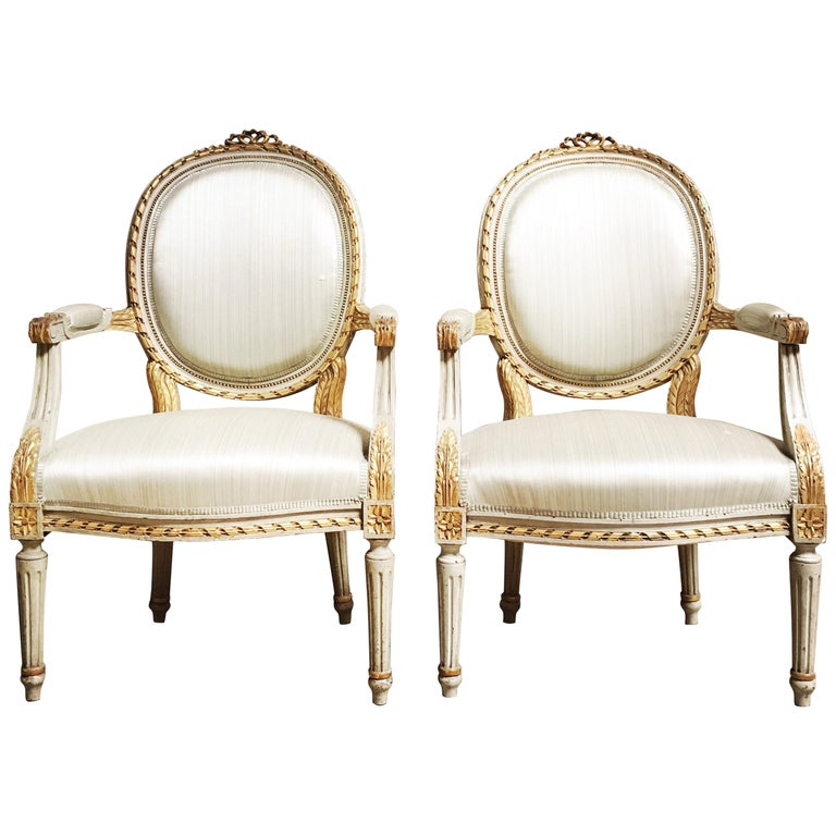 Pair of French Louis XVI Style Painted and Parcel Gilded Fauteuils