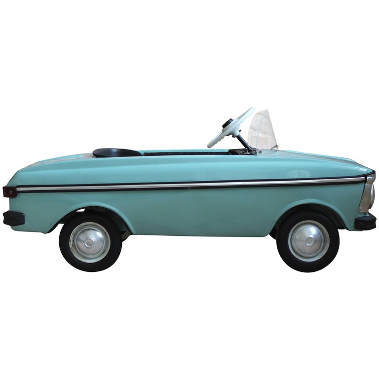 This early Soviet child's pedal car was manufactured during the communist era in former Czechoslovakia. It was created as a model for children as a small copy of the original Moskvich car and works on a pedal moving system. The piece features fully