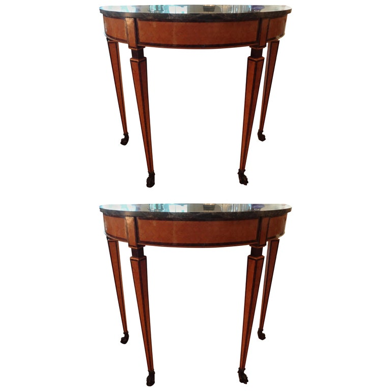 Matching pair of 19th century Italian Neoclassical style parquetry console tables. This pair of Antique Italian demilune tables have a beautiful fruitwood geometric inlaid design with paw feet and marble tops.
