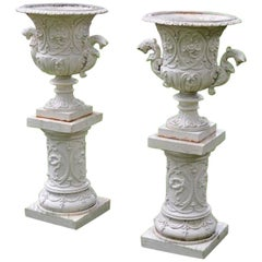 Pair of White Painted Cast-Iron Urns on Pedestals