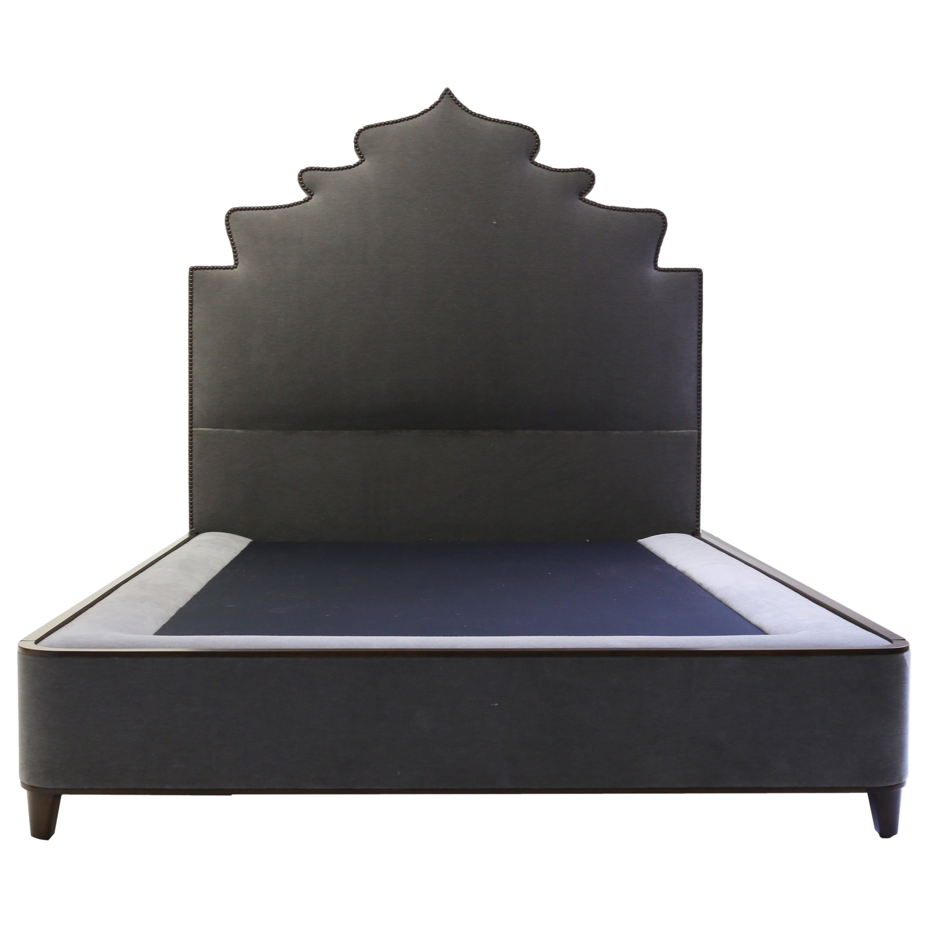 Queensize Bed with Carved Headboard with Nailheads and Covered Base on Wood Legs