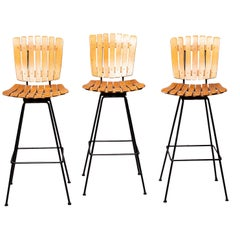Three Midcentury Arthur Umanoff Slatwood and Iron Swivel Bar Height Stools