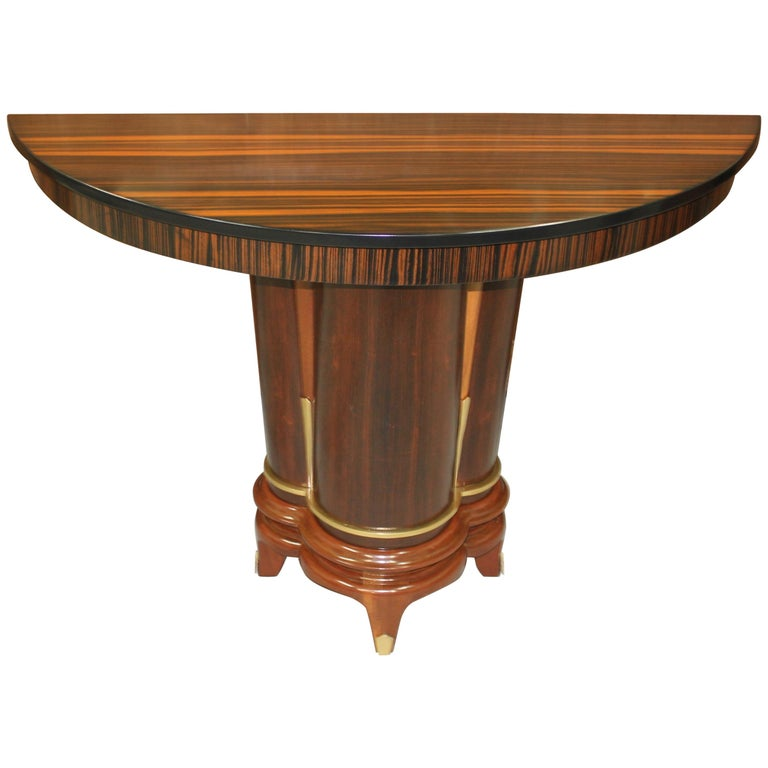 Classic pair of French Art Deco exotic Macassar ebony console tables, circa 1940s. Beautiful Macassar ebony with demi lune Macassar top and beautiful center base , lacquer finish in both side, beautiful bronze hardware detail, that rest on makes it