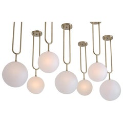 Koko, a Modern Pendant Light with Satin Globe Shade in Brushed Brass Finish