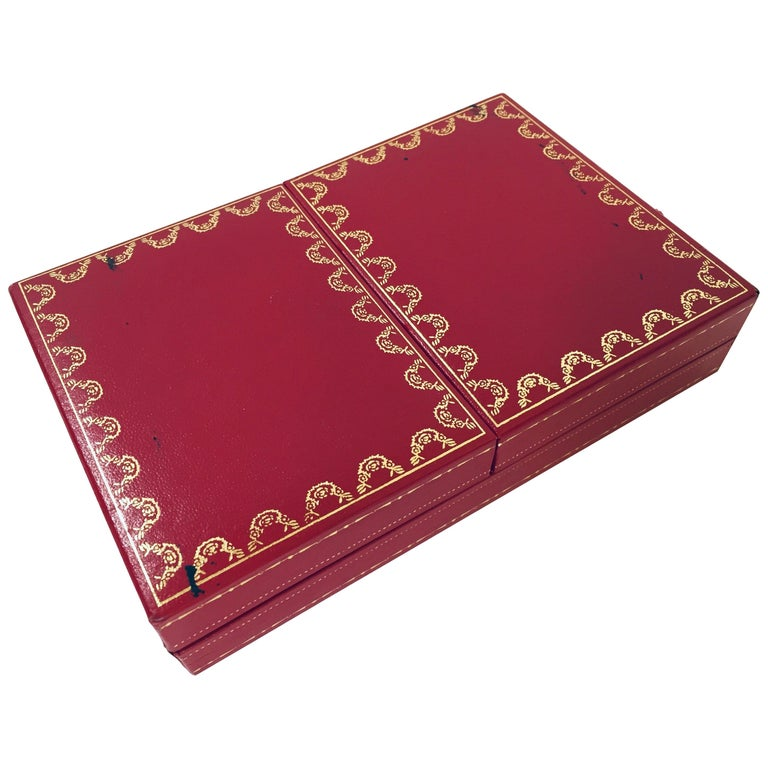 Cartier playing cards, one deck plus joker, poker, bridge playing cards in Cartier red 2-doors case. Les Must de Cartier playing cards were only sold from 1972-1976.  This silk-lined box of cards with 18k gilted corners, printed with the Les Must de