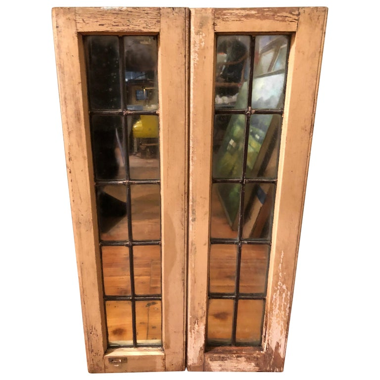 Pair of Shabby Chic leaded glass mirrors. Nice architectural pieces to install in a country home or just hang on the wall to give a room depth. Cream colored chippy paint and leaded grills. Each window is wired to hang vertically. Can be wired to