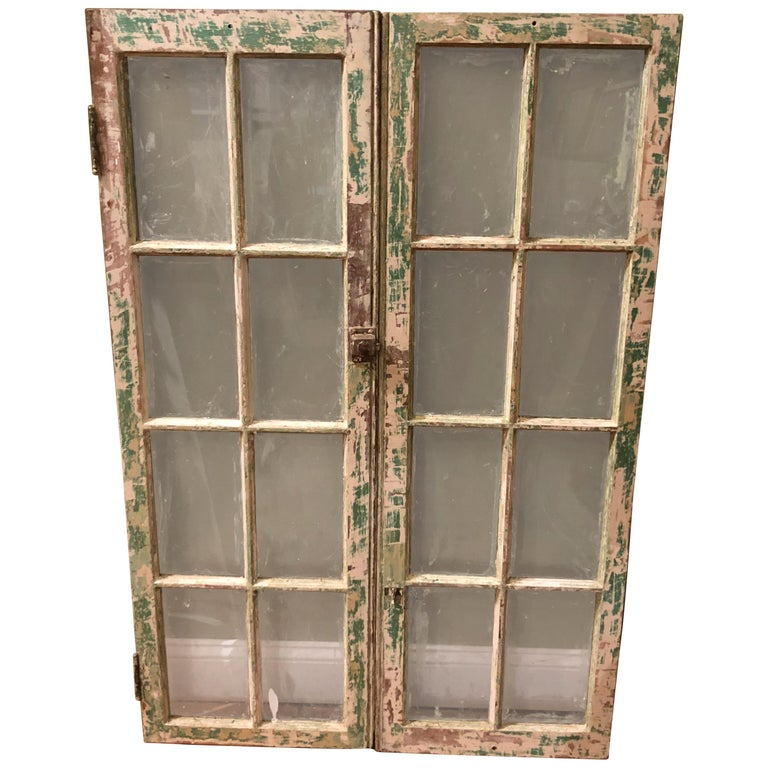 Pair of antique windows with distressed green paint finish. Use as real windows or add a mirror back to them and hang on a wall. Great architectural pieces for a farmhouse or country style home. Pair measures: 48.25 H x 32.25 W x 1.50 D. Each window