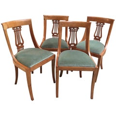Set of Four French Neoclassical Fruitwood Lyre Back Chairs with Falcon Heads