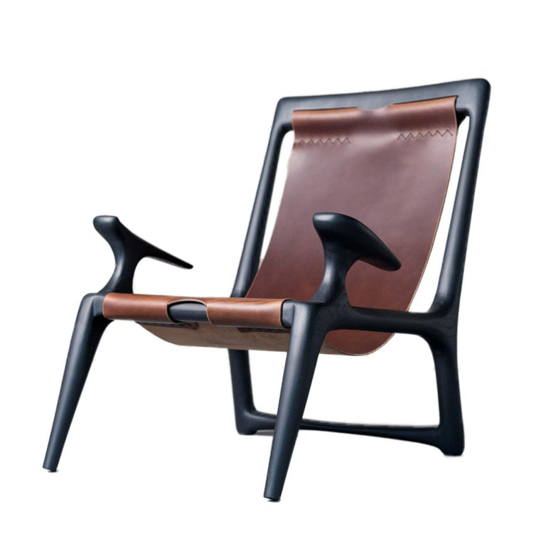 This award winning piece is the inaugural chair design by Fernweh Woodworking. The frame is hand-shaped from high quality American ash stained charcoal black, with sleek joinery inspired by Danish, Scandinavian, and Mid-Century Modern design. Slung