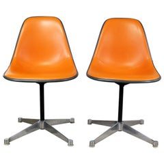 Pair of  Eames PSC Orange Vinyl Upholstered Pivoting Side Shell Chairs