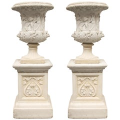 Pair of Cast Neoclassical Urns on Plinths