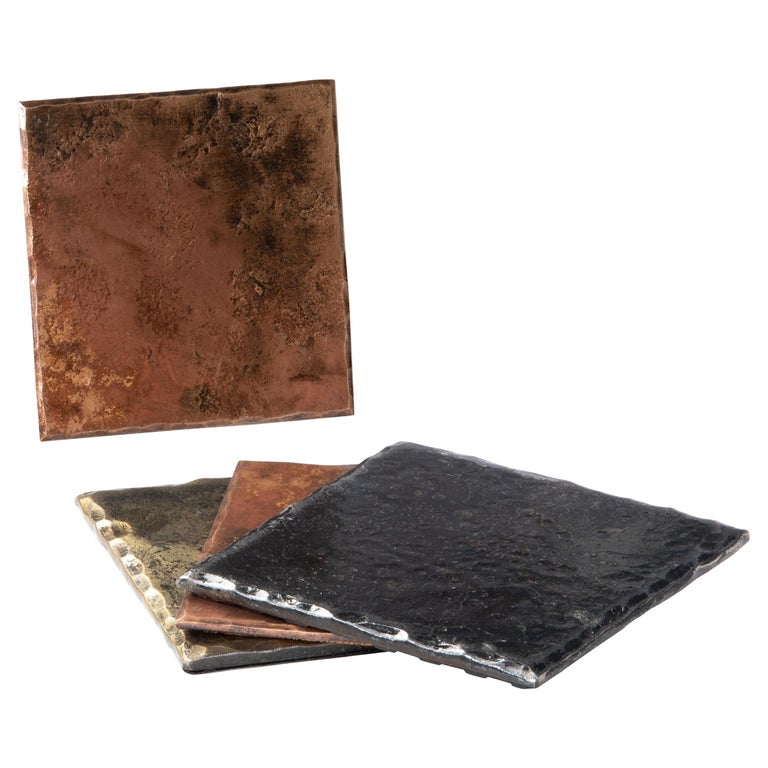 A handcrafted, square coaster made from bronze that has been forge textured over a rough steel anvil face to provide texture. The edges are hammered and beveled. The bronze is burnished to accentuate the forged details. The oxidized, brushed surface