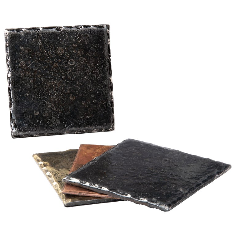 A handcrafted, forged, steel square coaster with hammered, bevelled edges that have been polished. Wire brushed and lightly sanded to accentuate the contrast between the edges and the surface. A glossy clear coat enhances the richness of the finish