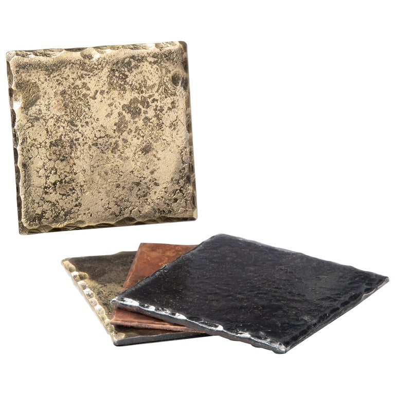 A handcrafted, steel square coaster with hammered, beveled edges. The rich gold tone is achieved through the use of a brass wire brush. A glossy clear coat enhances the richness of the finish and texture. Thin cork base. Sold as a set of 4.