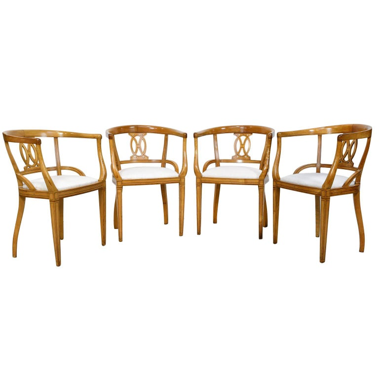 A set of four very handsome Scandinavian Biedermeier armchairs in blond birchwood with barrel-back and tapered legs, circa 1835. Chairs features ebonized wood, line inlays that accentuates the geometrical pattern on the carved back-splat and