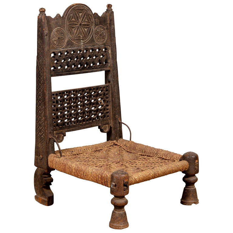 antique indian rustic low seat wooden chair with fretwork accents and rosettes for sale at 1stdibs