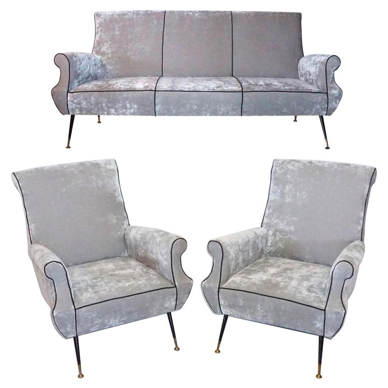 A vintage Mid-Century Modern Italian silver seating ensemble designed by Gigi Radice and produced by Minotti. Two lounge chairs and one three-seat sofa on conical iron legs with brass sabots which have been reupholstered with a high quality silver