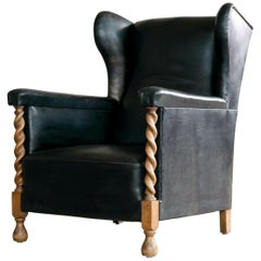 Danish 1930s Large Scale Club or Wingback Chair in Black Leather and Carved Oak