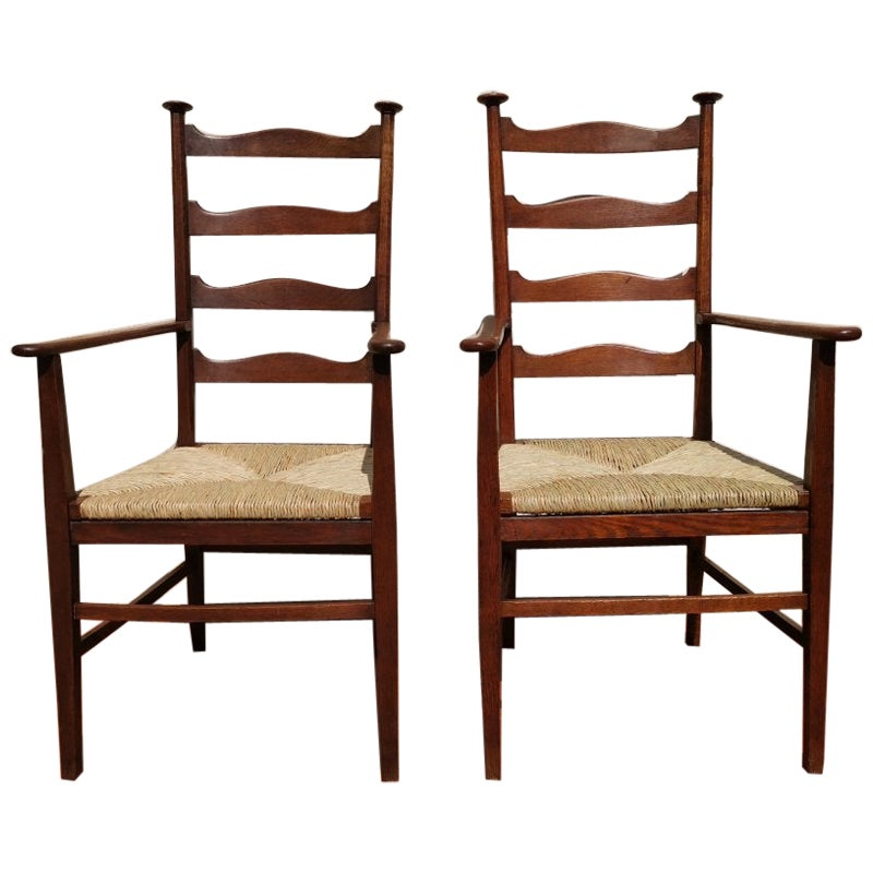 Liberty & Co. Style of Cfa Voysey, a Pair of Oak Rush Seat Ladderback Armchairs