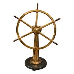 Solid Brass Ships Wheel Mounted Onto A Substantial Brass Pedestal