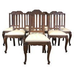 Set of Eight French Oak Intricately Carved Louis XV Chairs with Snail Feet