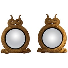 Pair of Regency Style Dolphin Giltwood and Parcel Ebonized Convex Mirrors