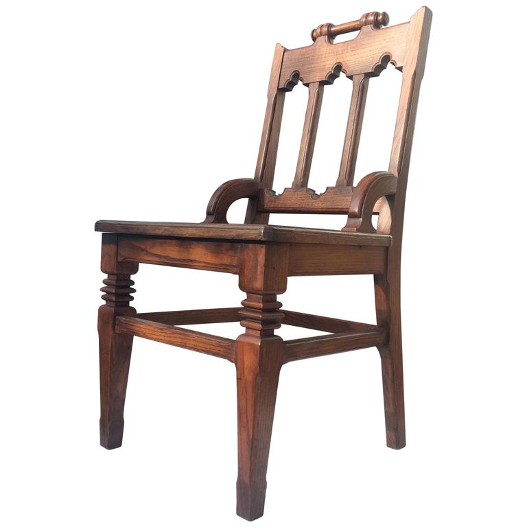 An early 20th Century English oak hall chair with Arts & Crafts and Gothic Style qualities. Handle back, carved graphic front legs. Excellent restored condition. *Requires drop in upholstered seat.