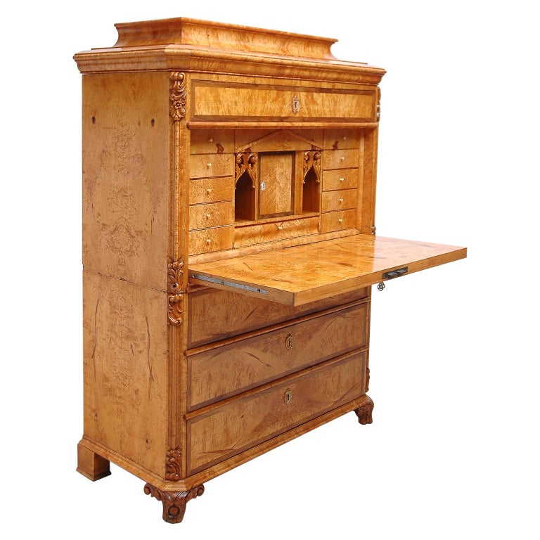 A handsome secretary abattant in birch, with birch root on drawer faces bordered in walnut. Offers a long drawer below pedestal top with desk top opening to many small drawers with two open compartments flanking a closed center cubby. Three large