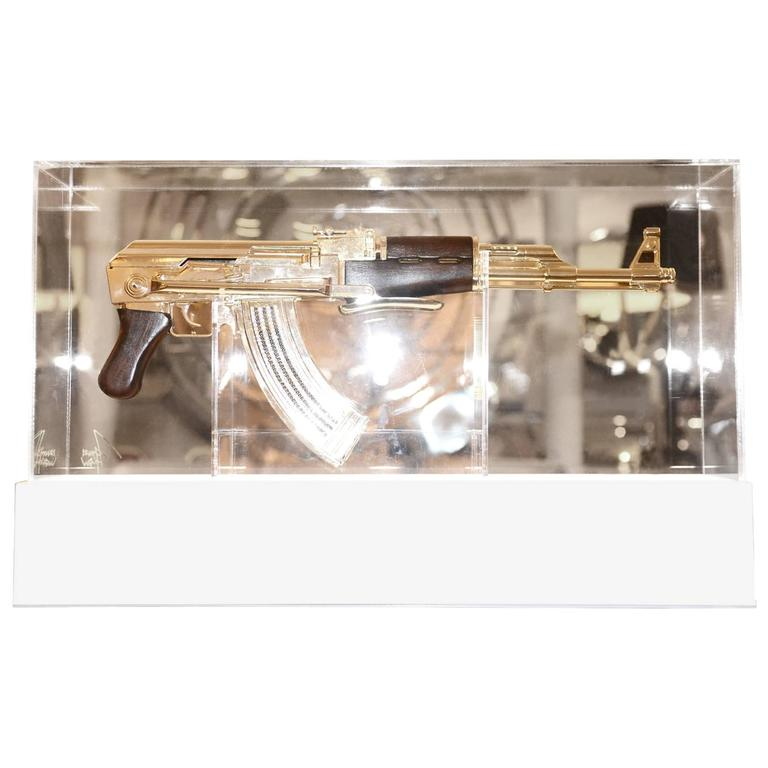 Assault rifle AK-47, in silver finish. Non-functional. Authentic limited edition piece, Numbered 04/05. Finish with silver. Base on plexiglass with led light and system of color variation and intensity. Incorporated. Transparent plexiglass