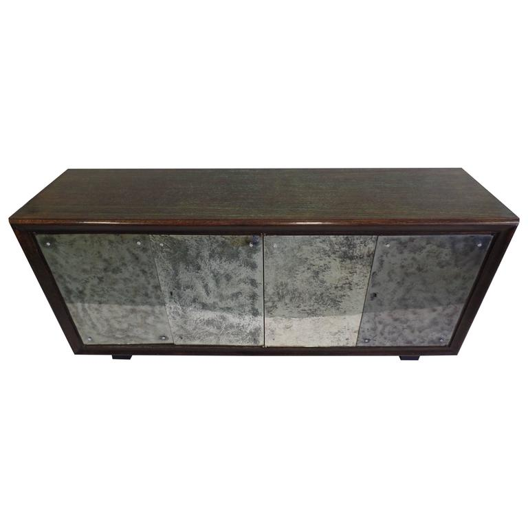 Elegant French Mid-Century Modern / Late Art Deco buffet, cabinet or console with sober modern detailing.   A rare and exquisite combination of dark oak that has been cerused green and mirrored doors in mercury patina creating a cloudy effect.