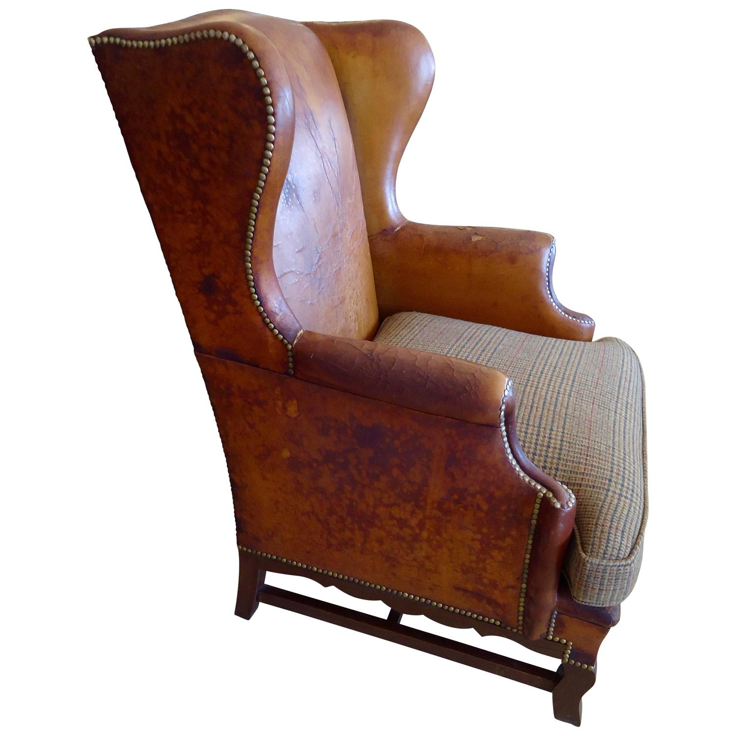 Much loved antique leather wing chair with upholstered for Antique leather chairs