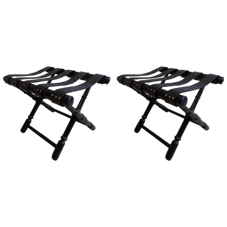 Elegant pair of French Mid-Century Modern Neoclassical benches, stools or luggage stands in delicately carved and ebonized wood with the bases arranged in a stunning X-form. The seats / tops are composed of straps of black leather each fixed with