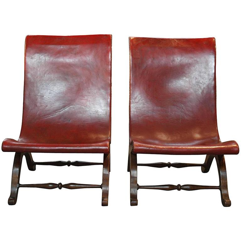 Pair of Spanish low slingback leather slipper chairs, ca. 1920