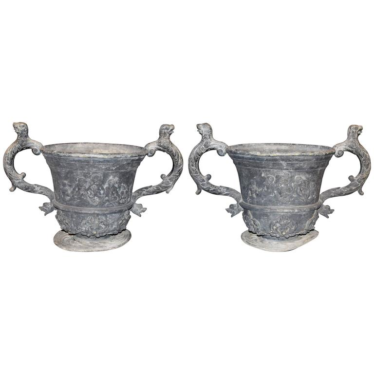 Pair of Lead Urns with Figural Handles and Cherub Decoration