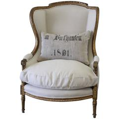 19th Century Louis XVI Giltwood Wing Chair Upholstered in Natural Linen
