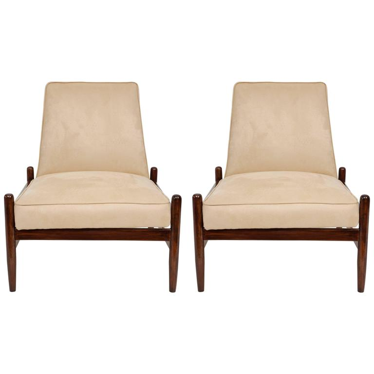 A pair of Brazilian modern lounge chairs, produced circa 1960s by Liceu de Artes & Oficios, back and seat upholstered in light beige faux suede, on jacaranda wood frames. Very good vintage condition, recently reupholstered.  10834