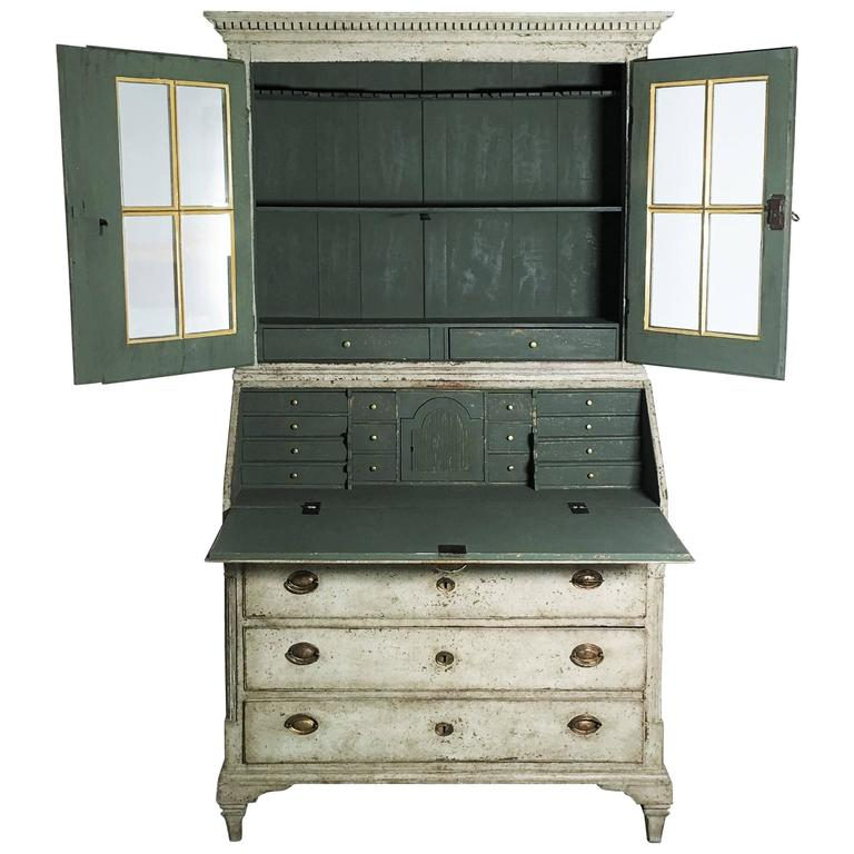 This is a rare and important Swedish Gustavian style painted secretary buffet with original brass hardware and locks, circa 1850. The upper china cabinet section has three shelves, the top shaped and slotted for spoons, behind door fronts carved