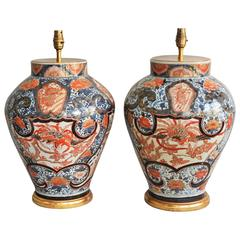 A Fine Pair of Early 18th Century Lamped Imari Vases on Gilt Bases