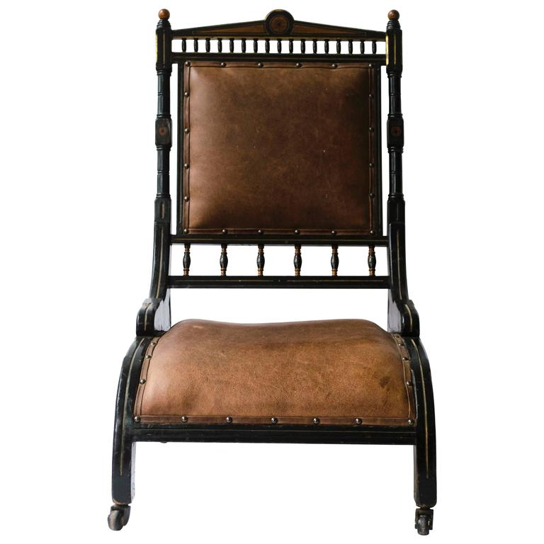 Richard Charles An Aesthetic Movement Ebonized and Parcel Gilt Lounge Chair.