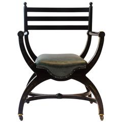 Richard Charles Aesthetic Movement Ebonised Elbow Chair with X Frame stretcher
