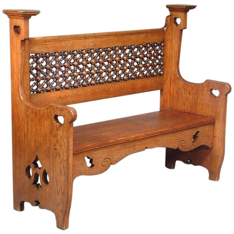 An Arts & Crafts Oak Settle by Liberty & Co with Mashrabiya turnings to the back
