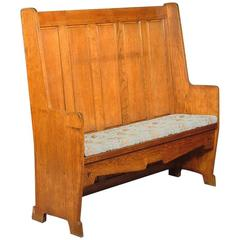 E A Taylor Attr, An Arts & Crafts Oak Panelled Settle with twin heart cut-outs.