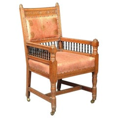 E W Godwin. An Aesthetic Movement Carved Oak Armchair with Ebonized Spindles