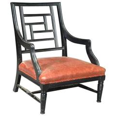 A Low Ebonized Elbow Chair, Attributed to E W Godwin.