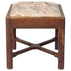 Gordon Russell An Arts & Crafts Oak Stool with drop in seat & a cross stretcher.