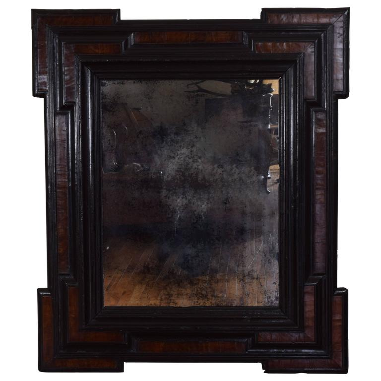 The frame having notched corners and raised moldings, walnut veneers and ebonized moldings, now fitted with an