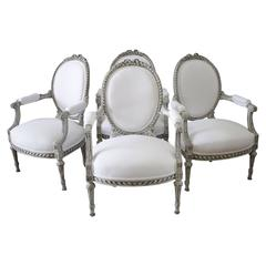 Four Painted and White Linen Upholstered Louis XVI Ribbon Carved Armchairs
