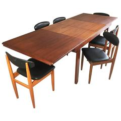 1970s Mid-Century Teak Extendable Dining Table and Six Black Vinyl Chairs